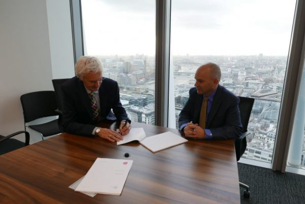 Quantex Arc Dr Paul Pankhurst signing paper in high rise office